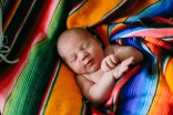 Photo of sweet newborn Ezra wrapped up in this bright blanket!