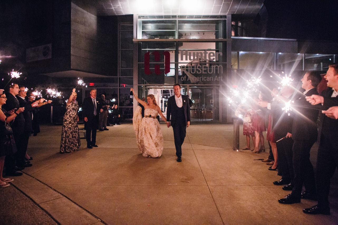 Bride and groom hold hands as they exit under the sparklers at their wedding at the Hunter Museum.