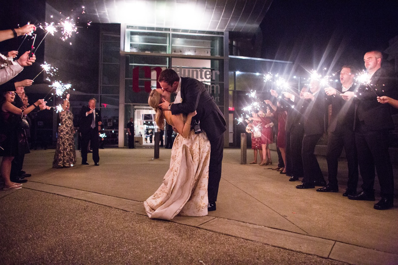 Groom dips bride for a kiss under the sparklers at the end of their wedding at the Hunter Museum.