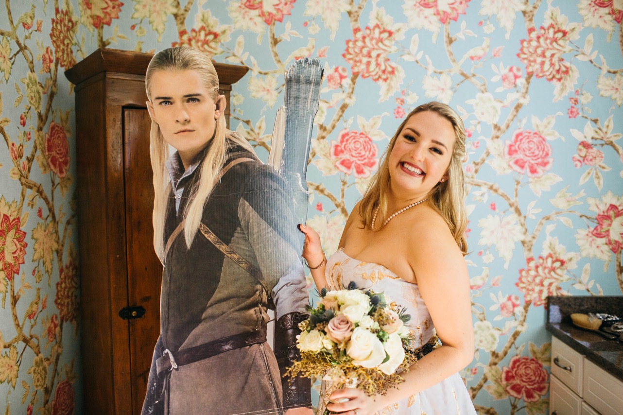 Bride smiles and holds a cut out of Legolas from The Lord of the Rings for her Hunter Museum wedding.