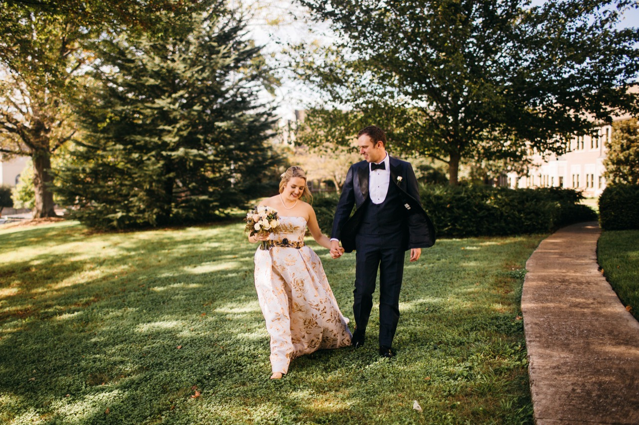 Bride and groom hold hands as they walk through the grass at their wedding at Hunter Museum.