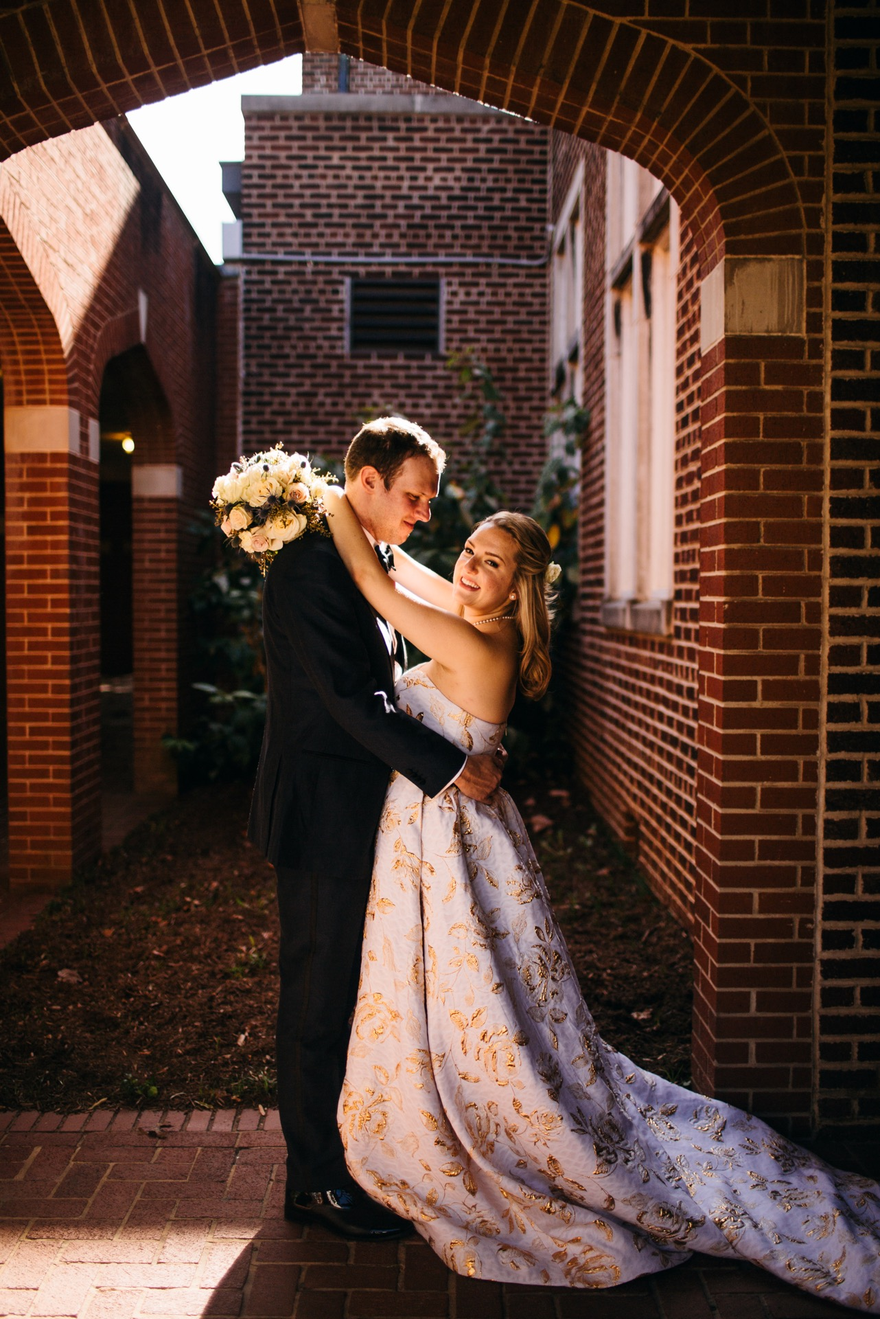 Bride throws her arms around groom and smiles at their Hunter Museum wedding.