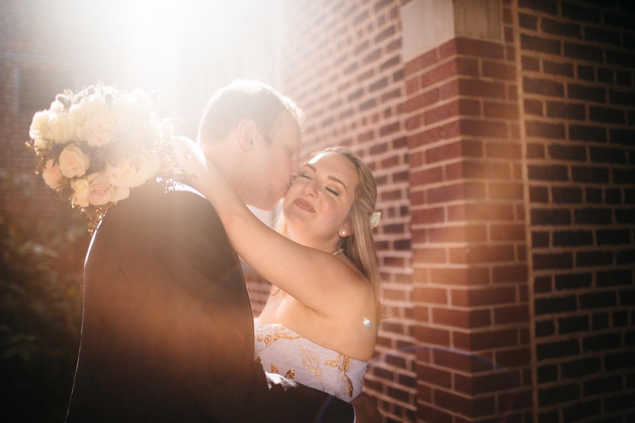 Groom kisses brides cheek at their wedding at Hunter Museum.