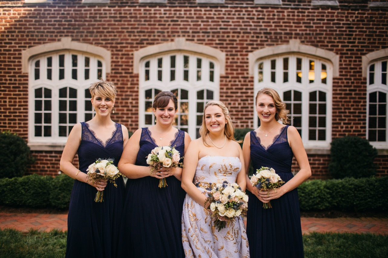 Bride and bridesmaids hold their bouquets and smile at the wedding at Hunter Museum.