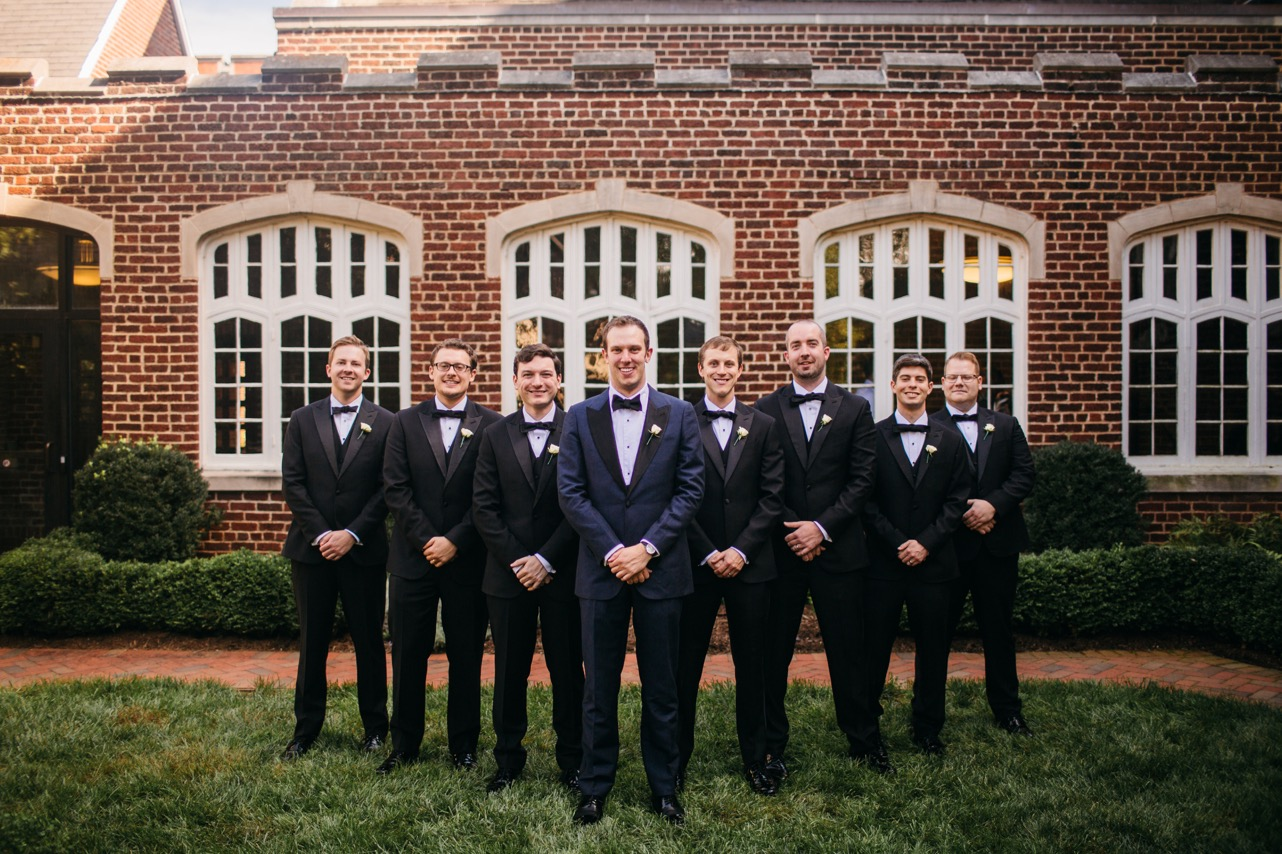 Groom and groomsmen hold their hands together and smile for the wedding at Hunter Museum.