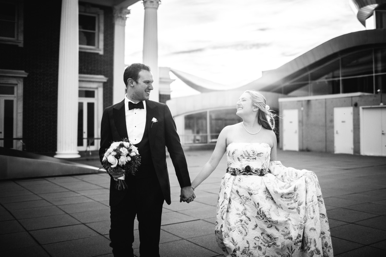 Bride and groom hold hands while smiling at each other at their wedding at the Hunter Museum.