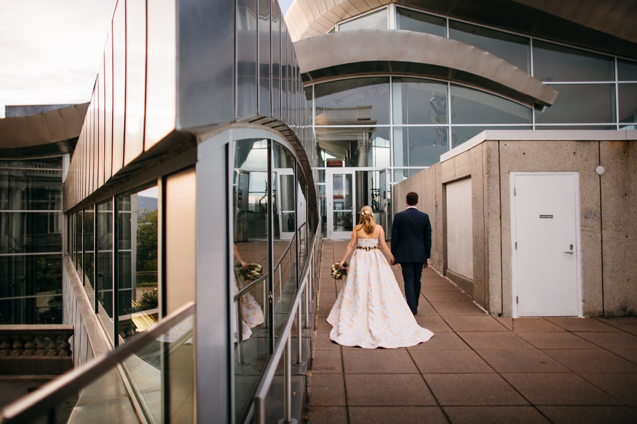 Bride and groom hold hands as they walk towards the reception of their Hunter Museum wedding.