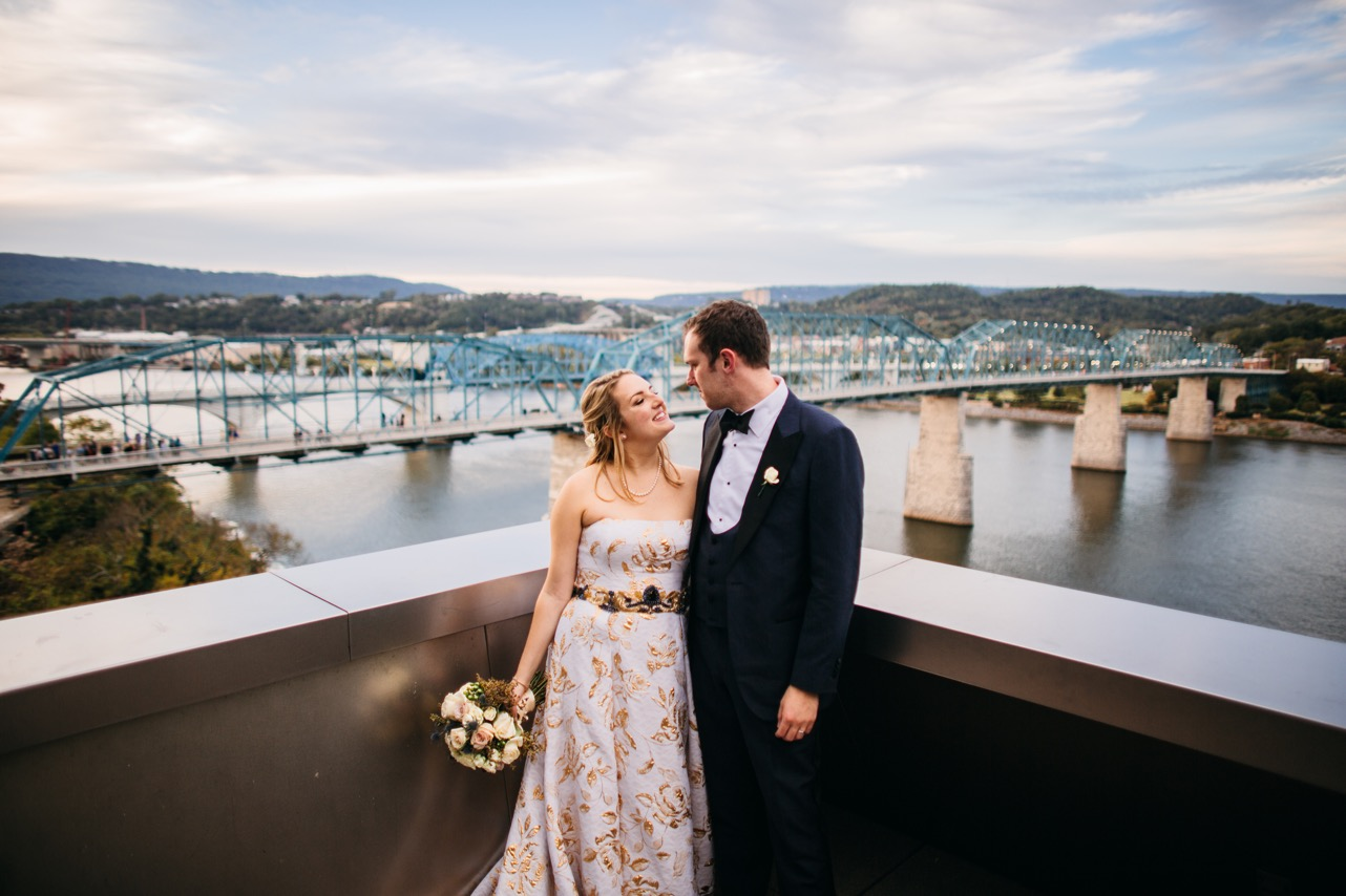 Bride and groom stand at the edge of the balcony and smile at eachother outside their Hunter Museum wedding.
