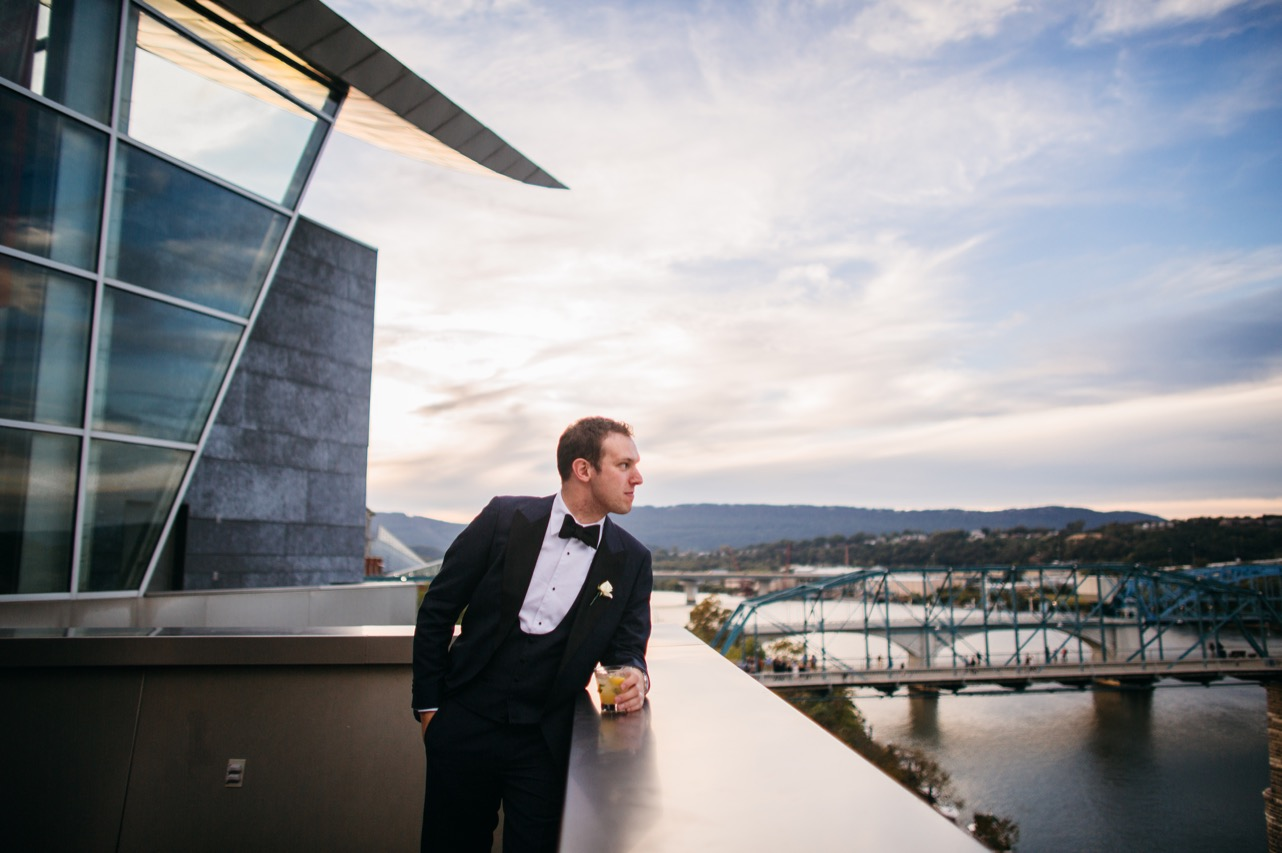 Groom looks over the balcony outside the wedding at the Hunter Museum.