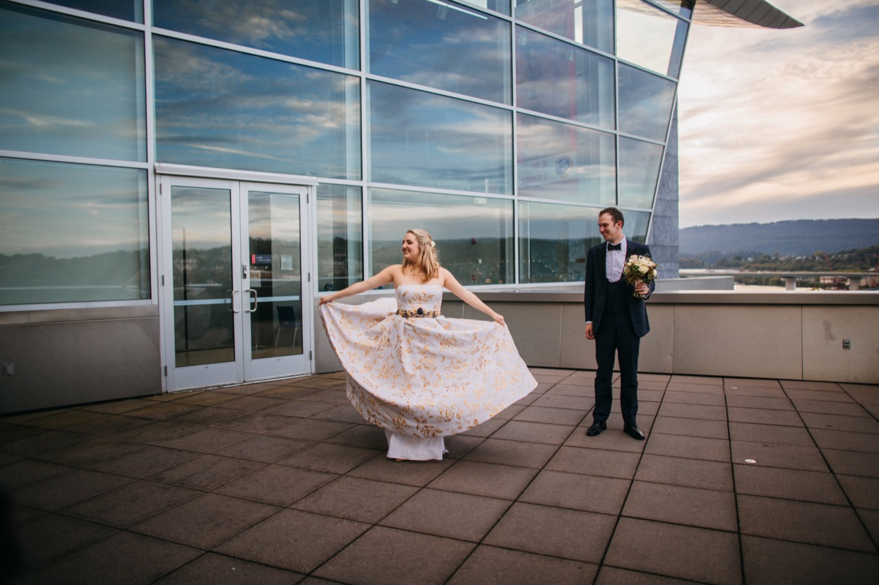 Bride twirls her dress on the balcony outside their Hunter Museum wedding.