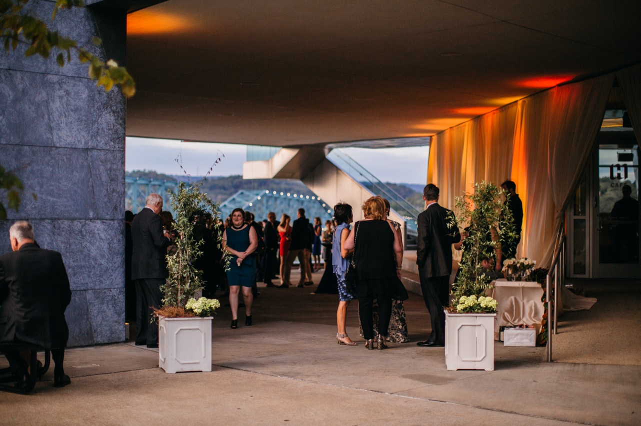 Family and friends mingle under the walkway during the reception at the wedding at Hunter Museum.