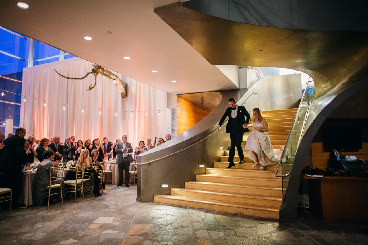 Bride and groom walk down the stairs of their wedding reception at the Hunter Museum.