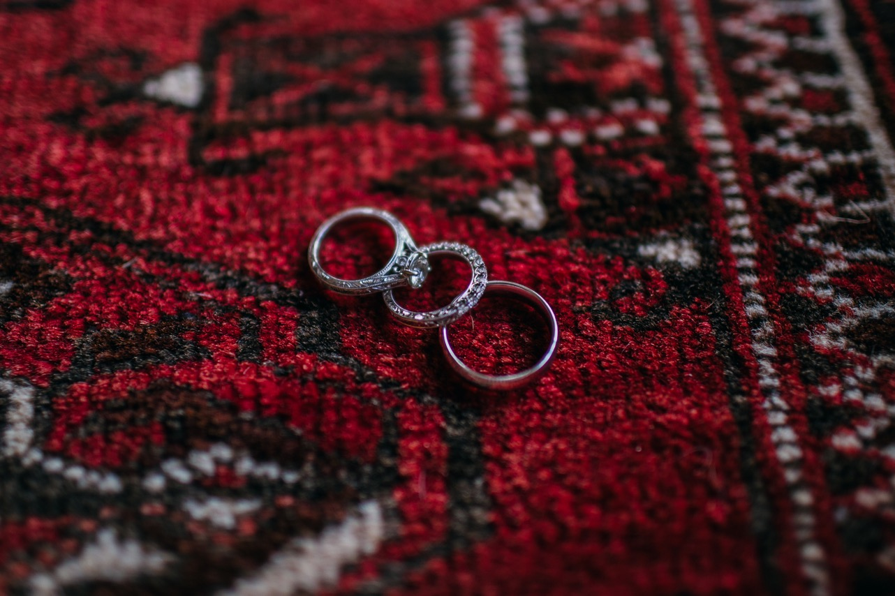 Bride and grooms rings are laid on a red rug inside the Hunter Museum