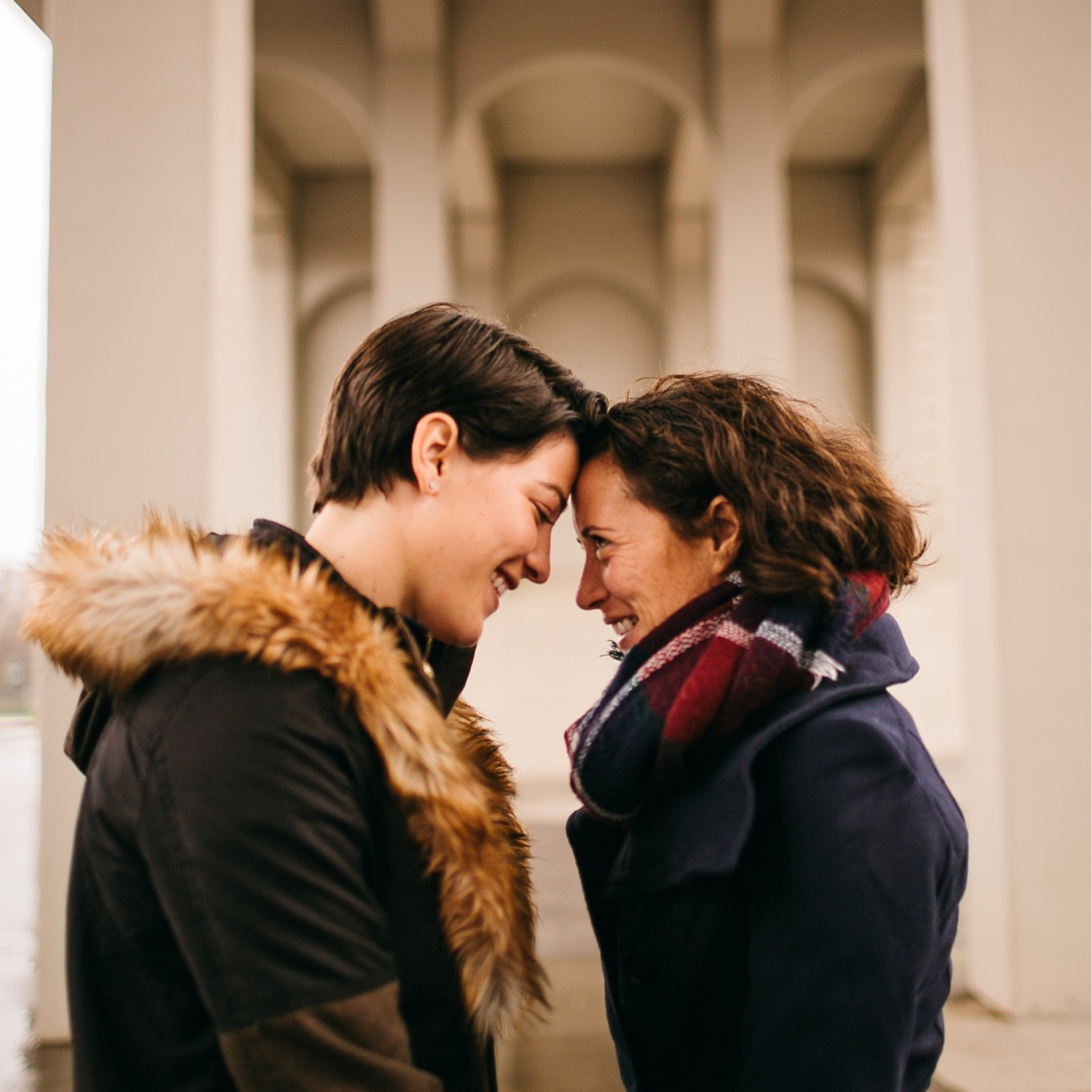A lesbian couple touches foreheads in front of a white stone background.