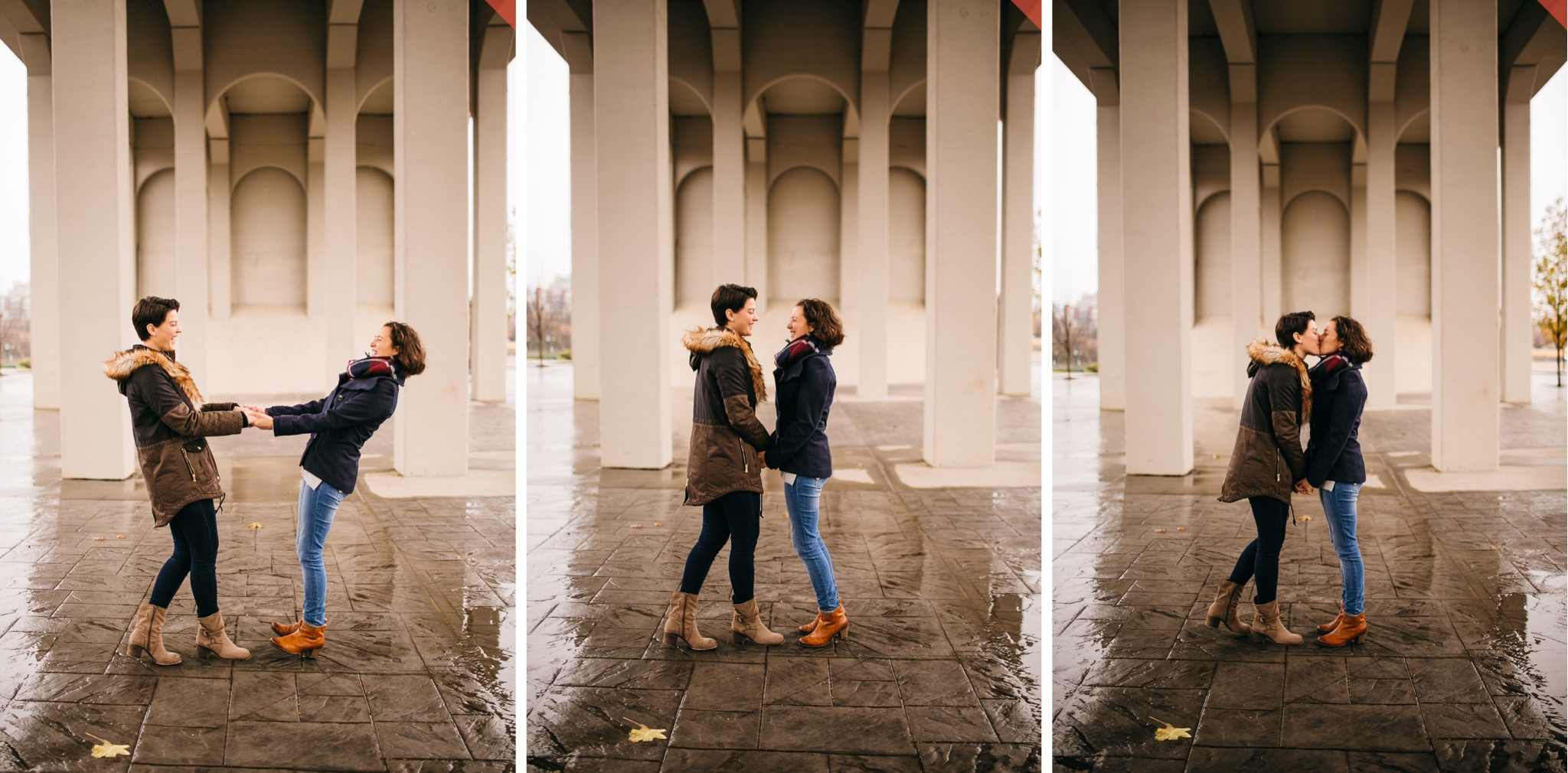 A lesbian couple dances in the rain under a white bridge.