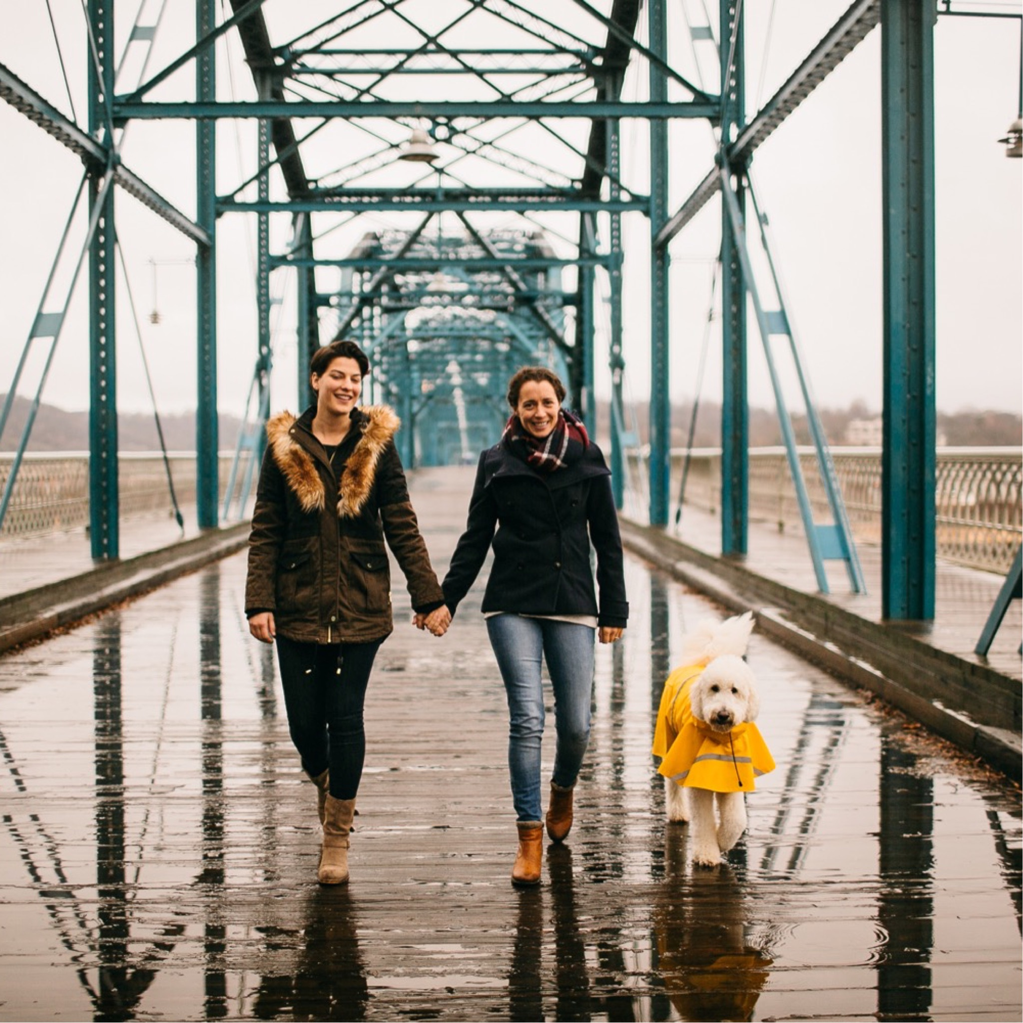 A lesbian couple holds hands on a bridge in the rain. They're walking their dog, a white goldendoodle in a yellow raincoat.