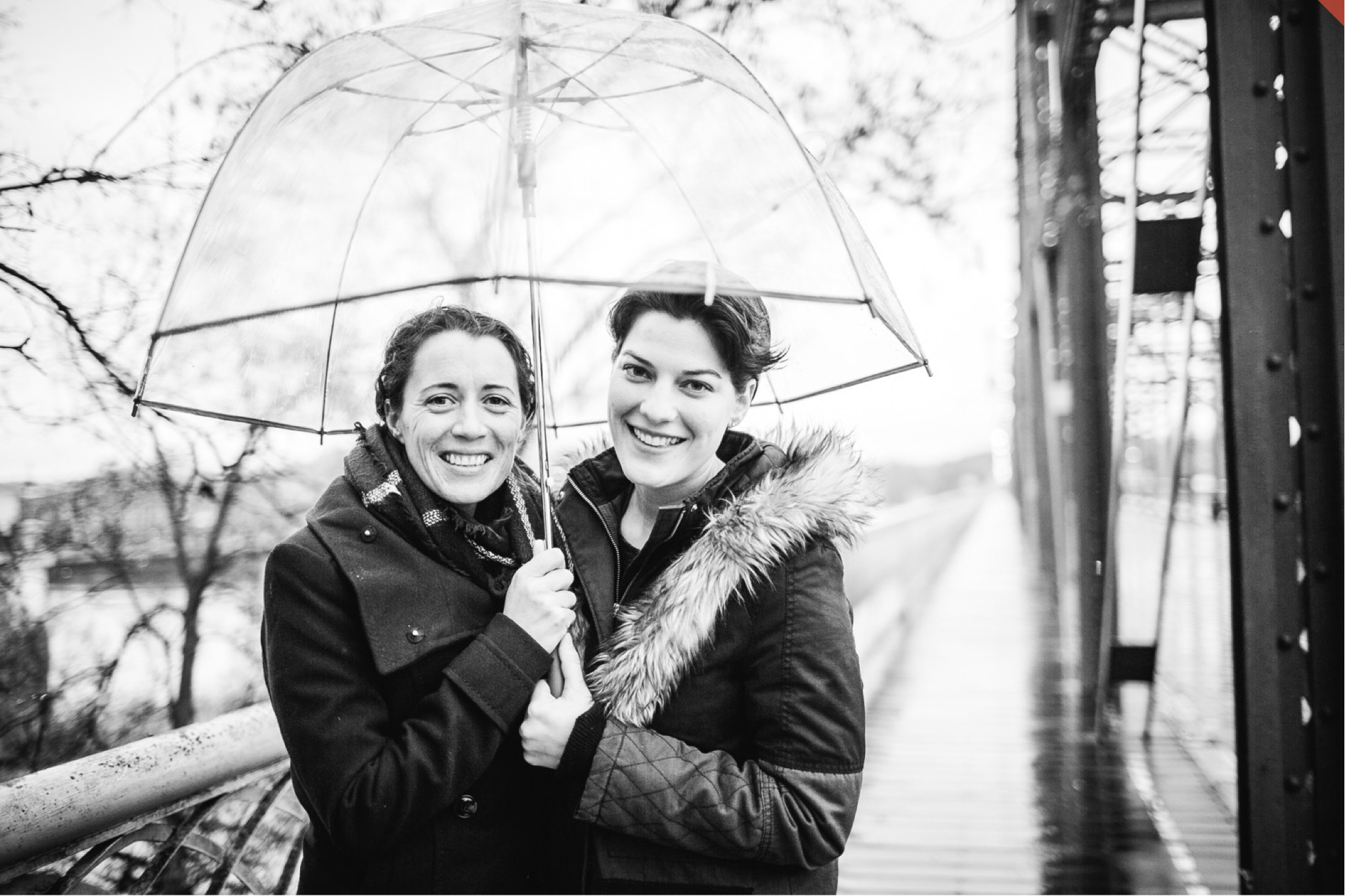 A lesbian couple poses underneath a transparent umbrella in the rain.
