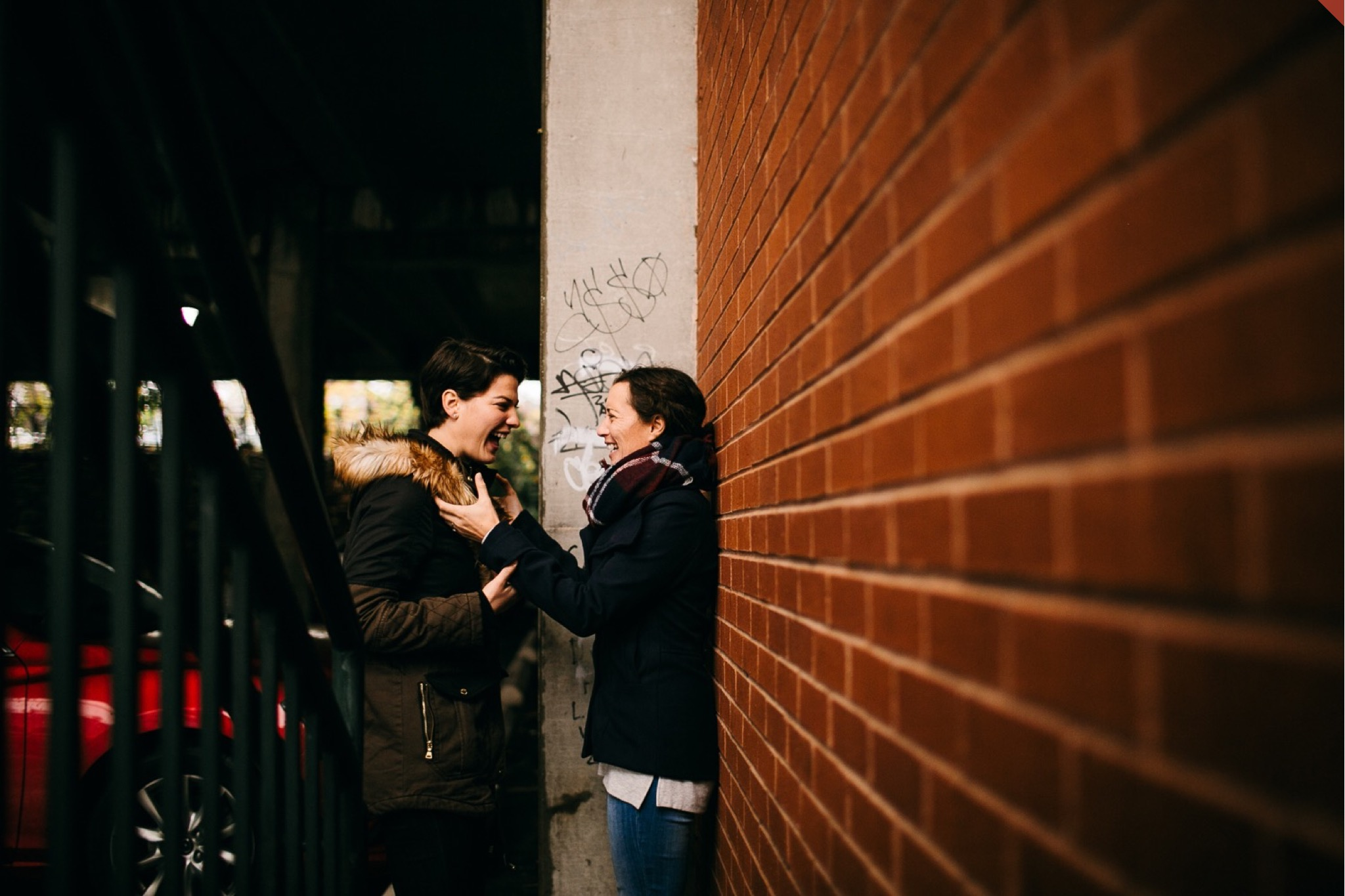 A lesbian couple embraces against a brick wall in a parking garage.