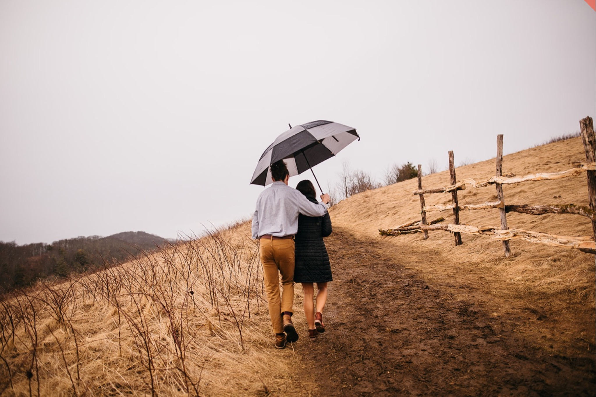 A couple hike to the top of Max Patch under an umbrella.