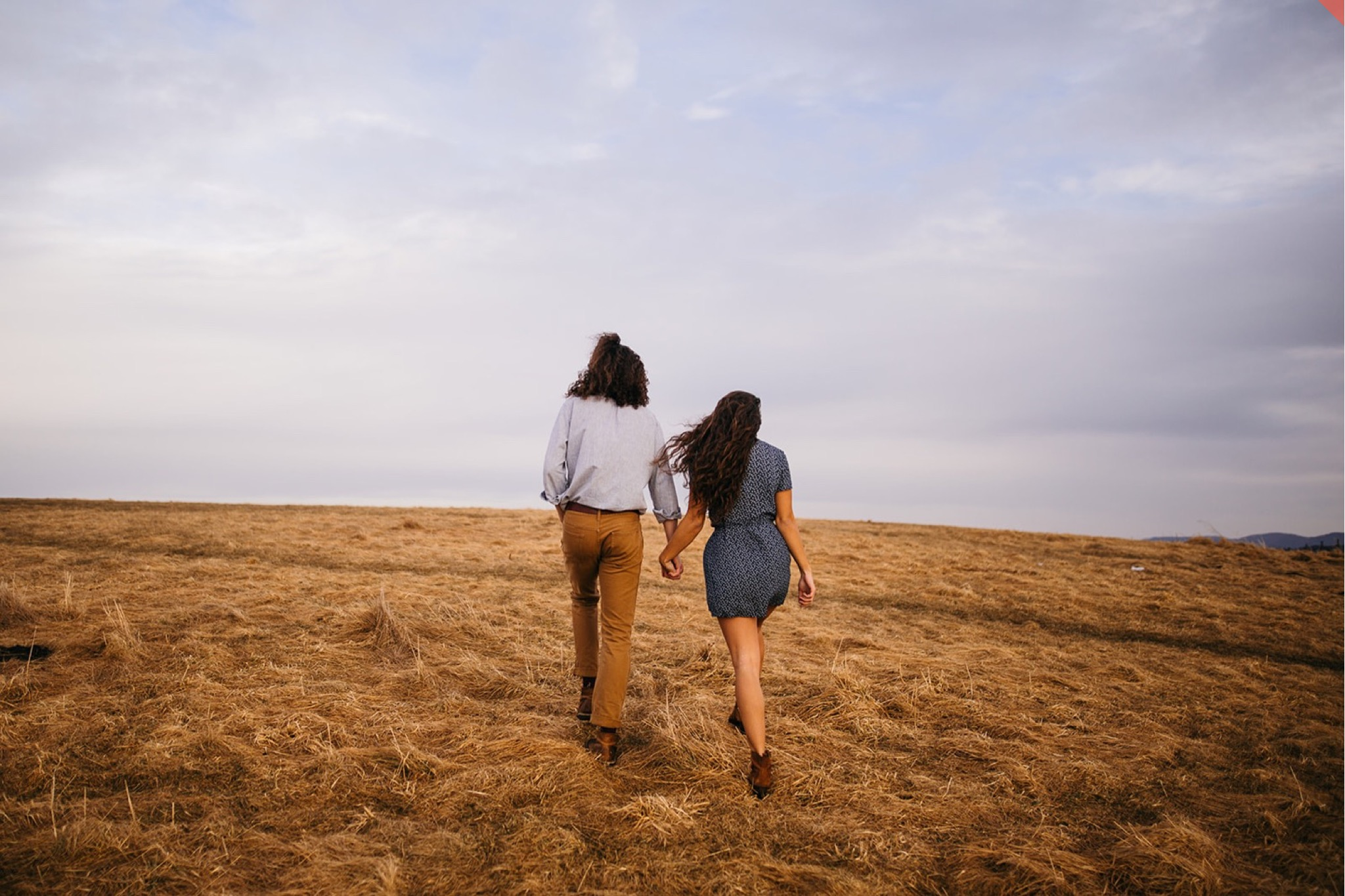A couple walk hand in hand at the top of Max Patch in North Carolina.