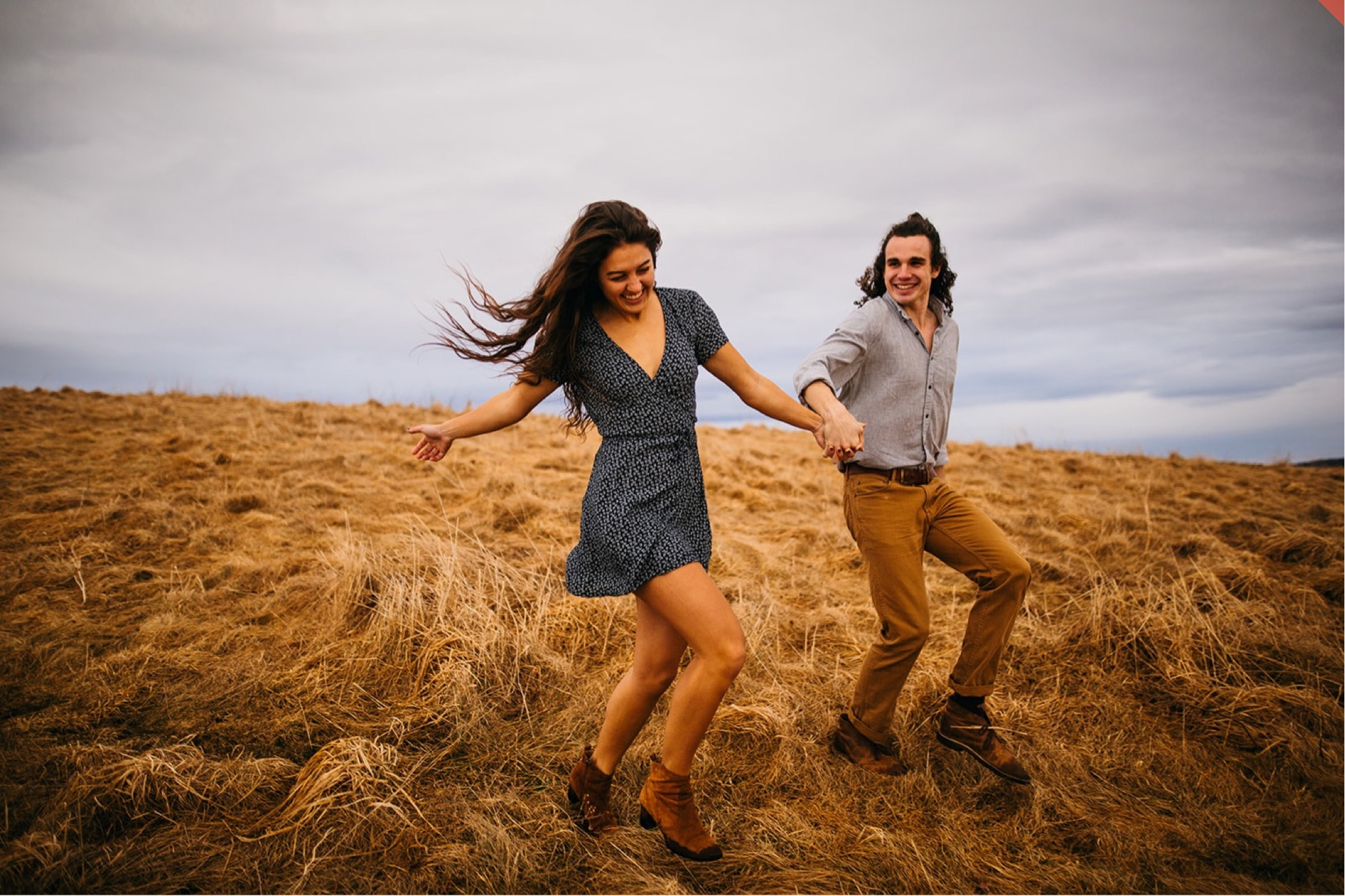 A couple runs together through dry grass on top of Max Patch in North Carolina.