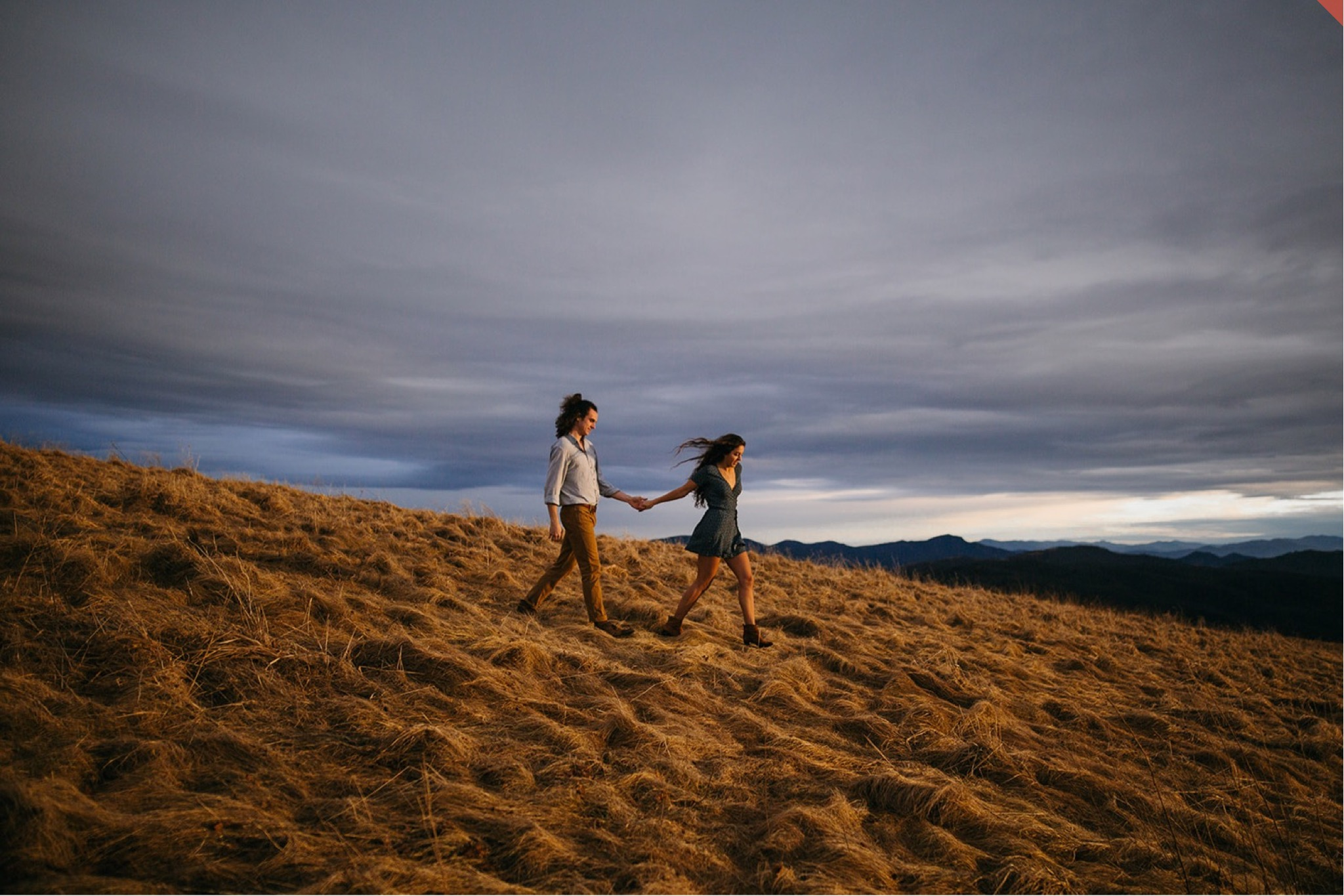 A couple walk together in the sunset light at the top of Max Patch.