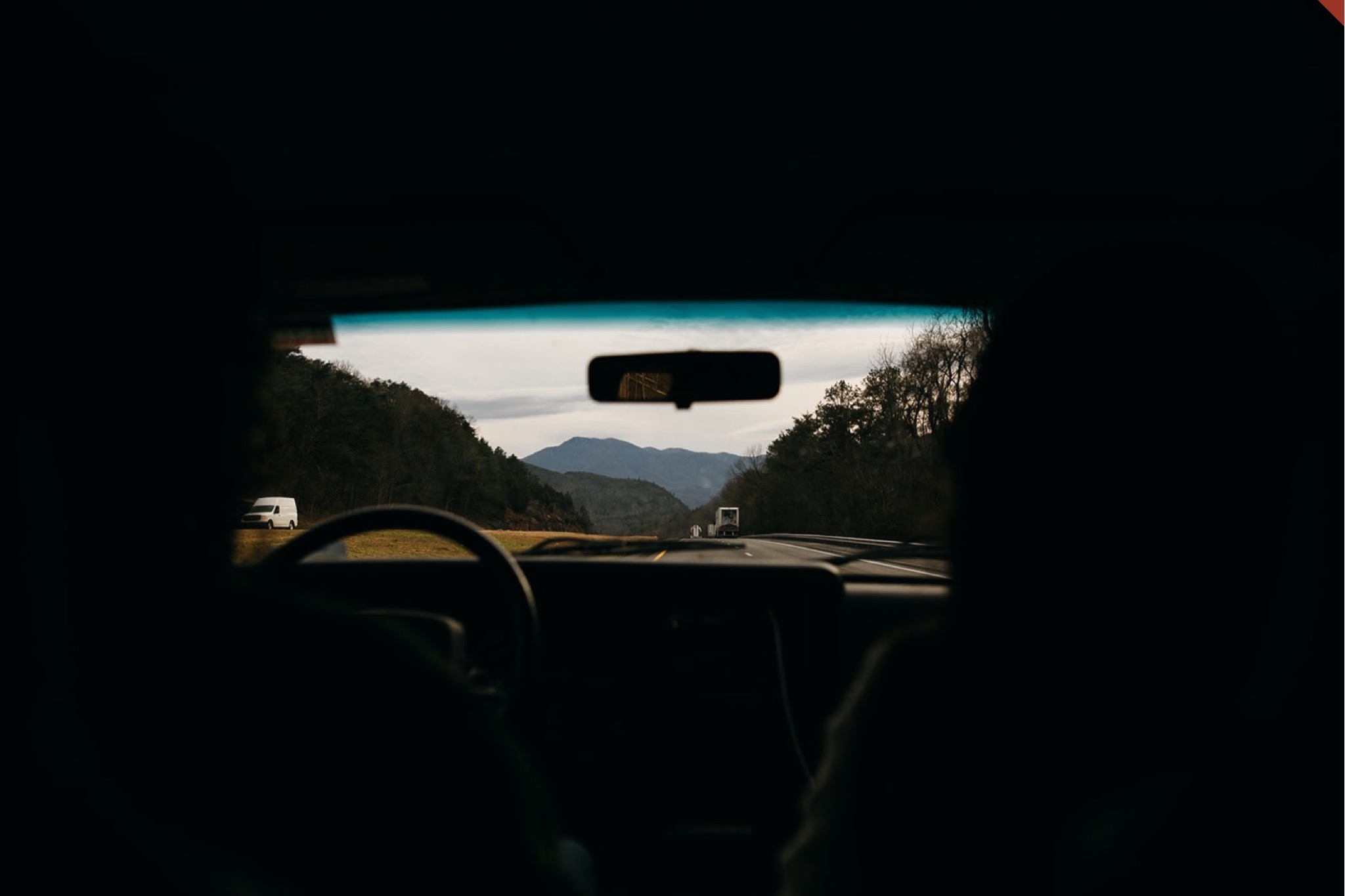 The view of hazy Blue Ridge Mountains through the windshield of an old Jeep.