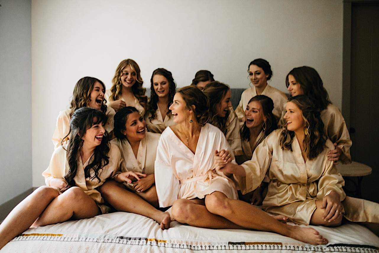 bride and several bridesmaids wearing satin bathrobes sit on a bed and laugh