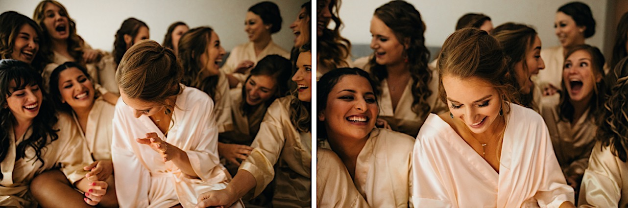 bride and bridesmaids laughing together while sitting in satin bathrobes on a bed