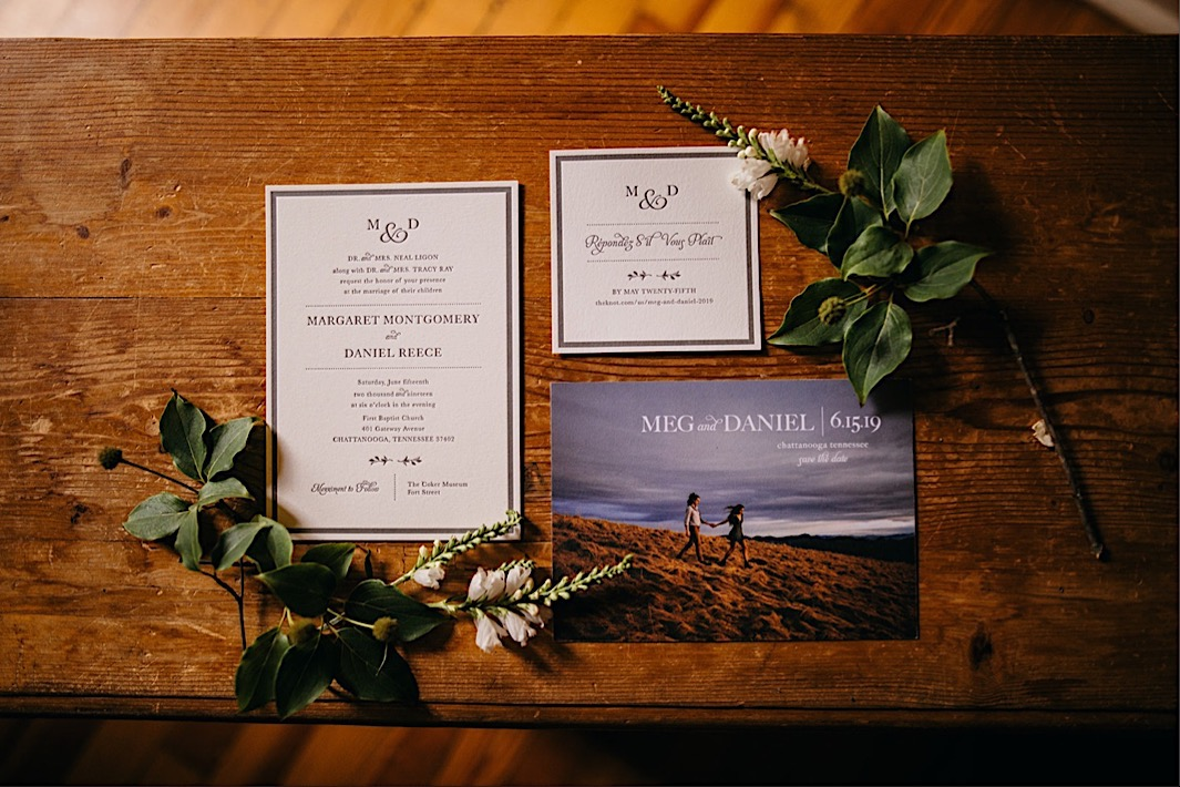 wedding invitation suite framed by greenery on wooden table