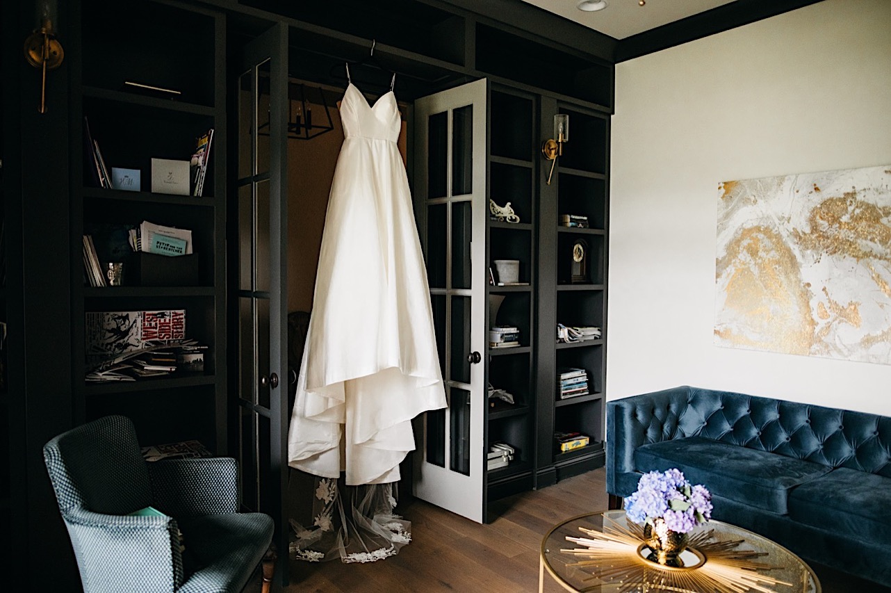 brides dress hangs in open french doors from a high black bookcase