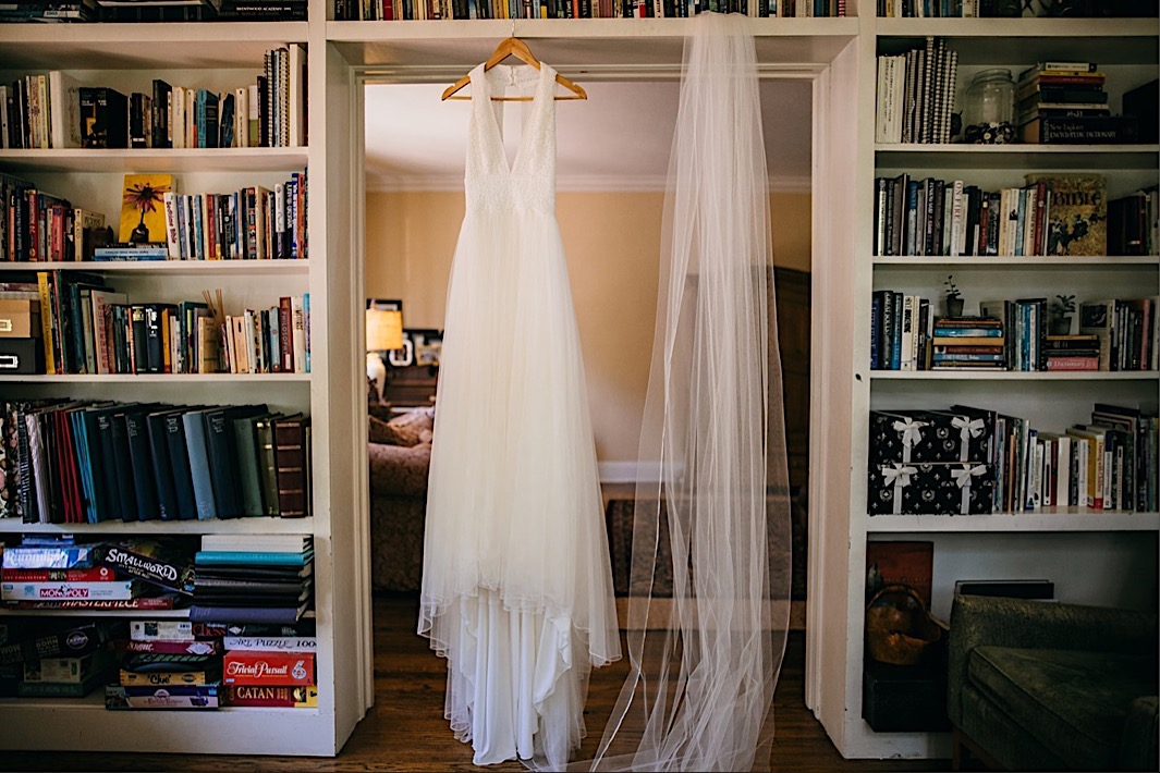 wedding gown hangs from a wooden hanger over a wide doorway with bookcases on either side