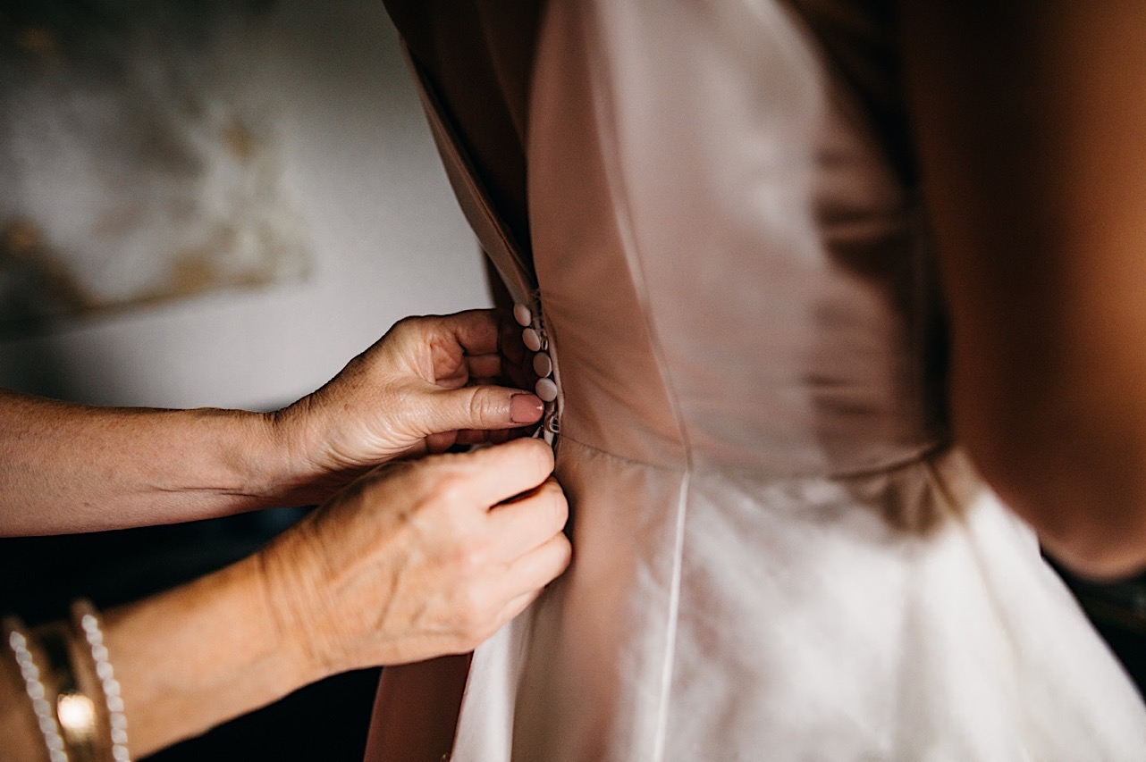 womans hands fastening the buttons on the back of brides wedding gown
