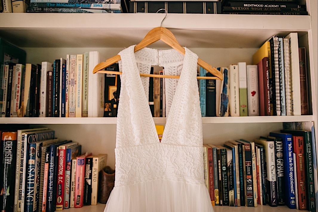wedding dress hangs from a wooden hanger on a full, white bookshelf