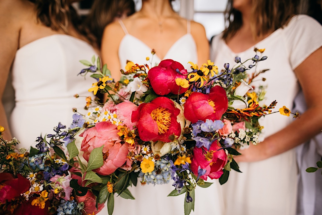 bride and bridesmaids extend their vibrant, organic Emily Kaye Designs floral bouquets