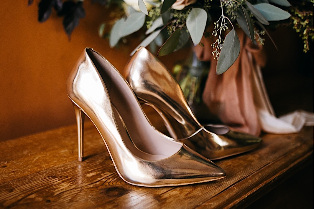 reflective silver pumps sit on a wooden table next to floral bouquet
