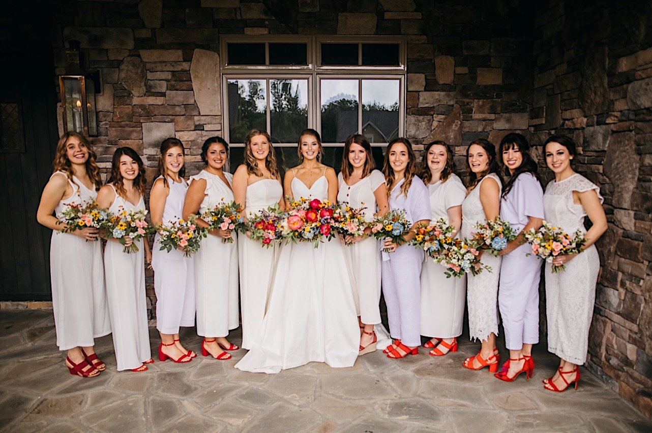 bride stands with bridesmaids in white jumpsuits and red heels. they hold colorful wedding bouquets by Emily Kaye Designs