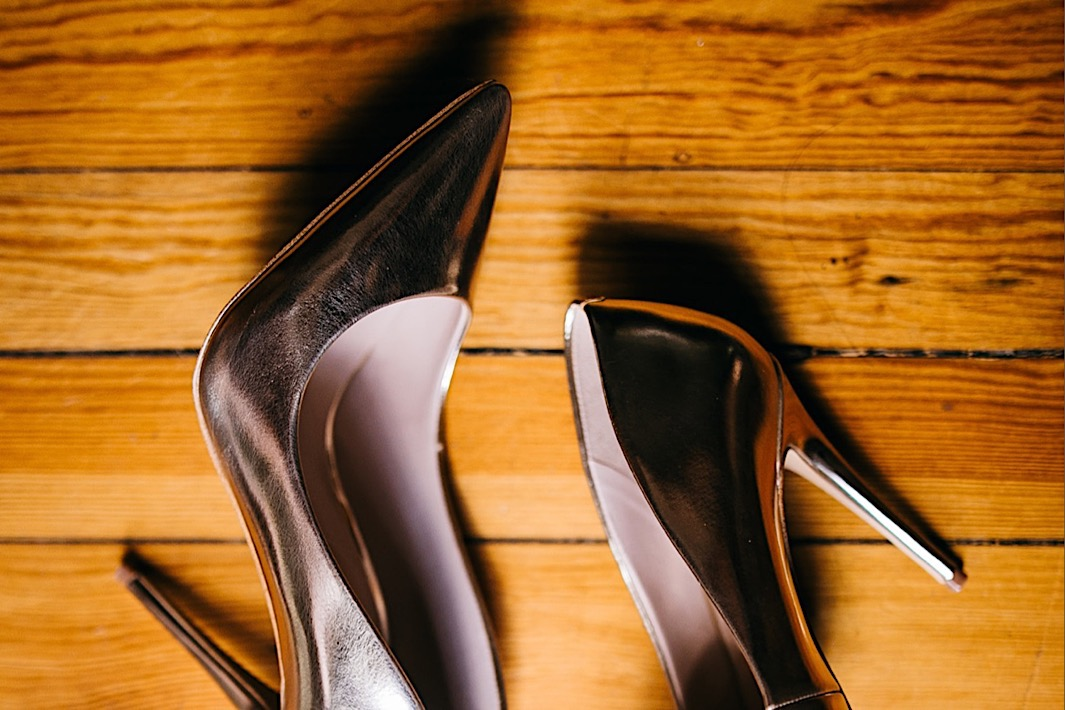 reflective silver pumps lie on a wooden surface
