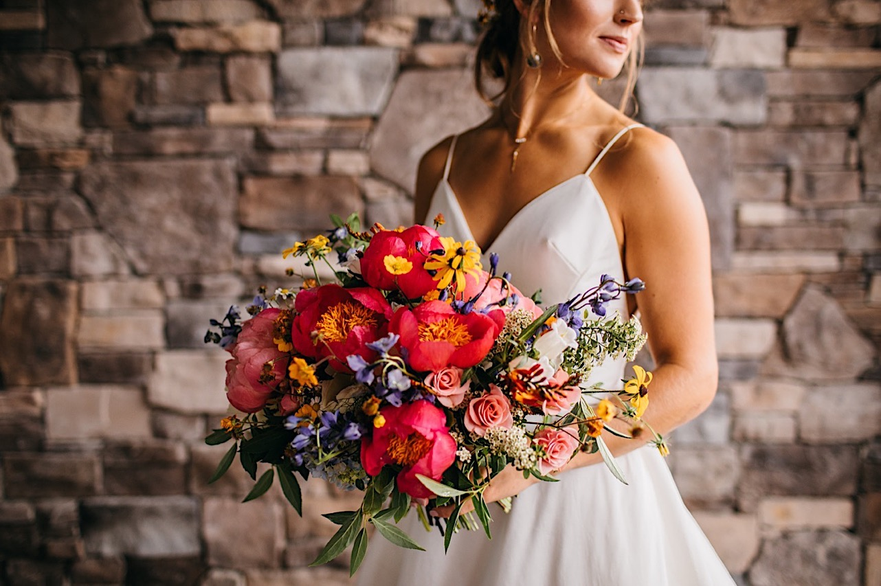bride stands looking over her shoulder in front of stone wall while she holds large, colorful floral arrangement by Emily Kaye Designs