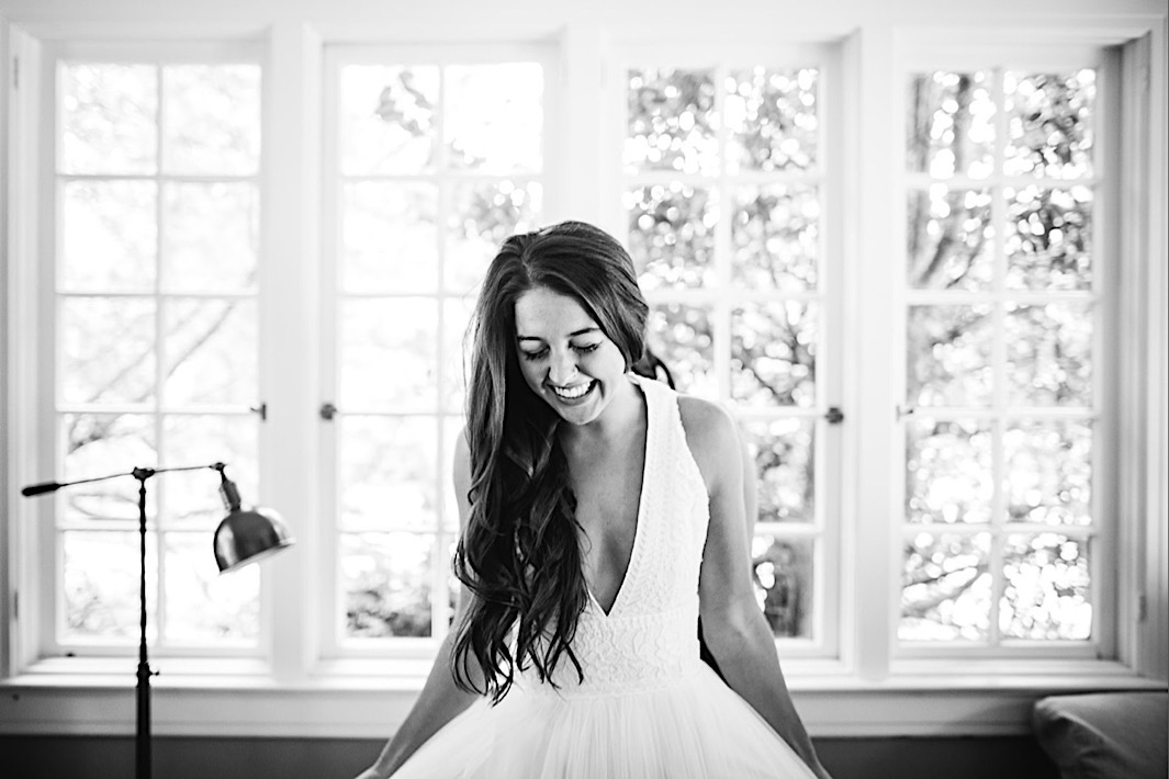 bride holds her tulle skirt out from her hips, laughing