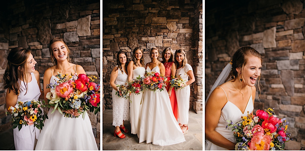 bride holds colorful Emily Kaye Designs flowers in front of stone wall and laughs with bridesmaids in white jumpsuits