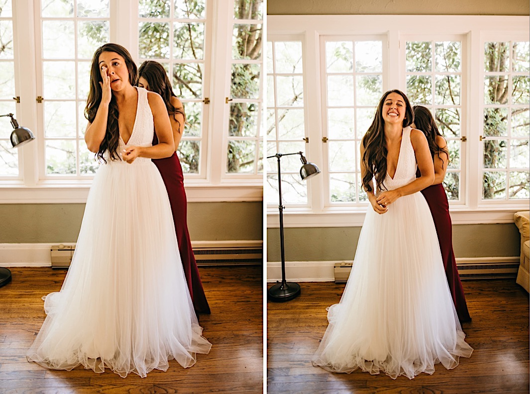 bride laughs and wipes her eye while her friend fastens the back of her dress