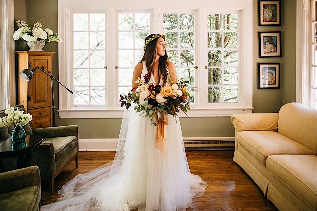 bride holds her large, organic Southerly Flower Farm bouquet with her tulle gown and veil pooled around her feet in a sunny room