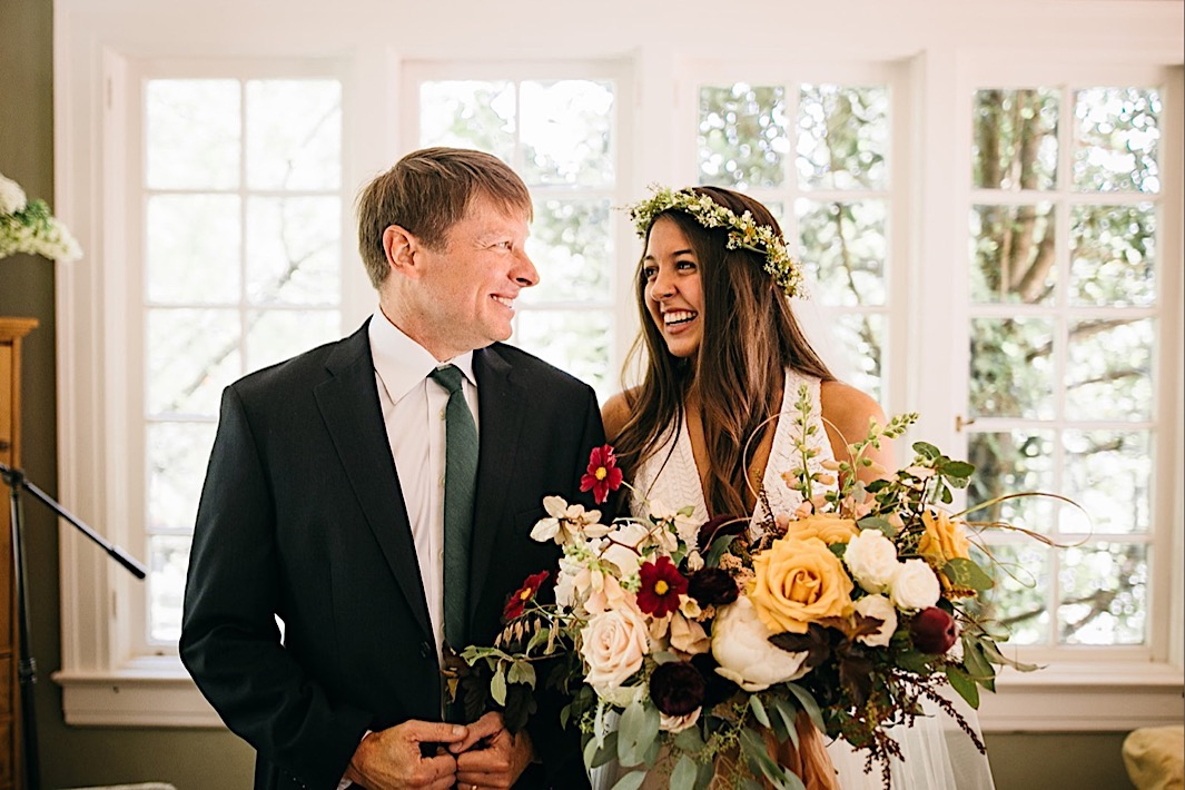 bride holds her giant, colorful Southerly Flower Farm bouquet and her father's arm and they smile at each other in a sunny room