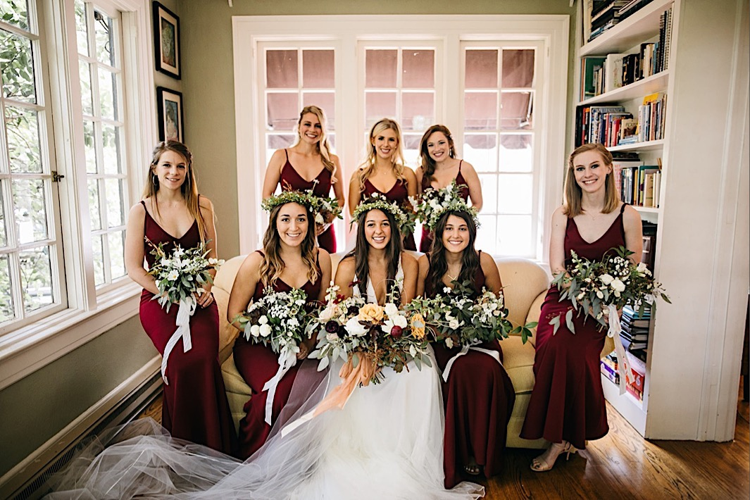 bride and bridesmaids sit on a cream sofa in a bright room holding their Southerly Flower Farm bouquets