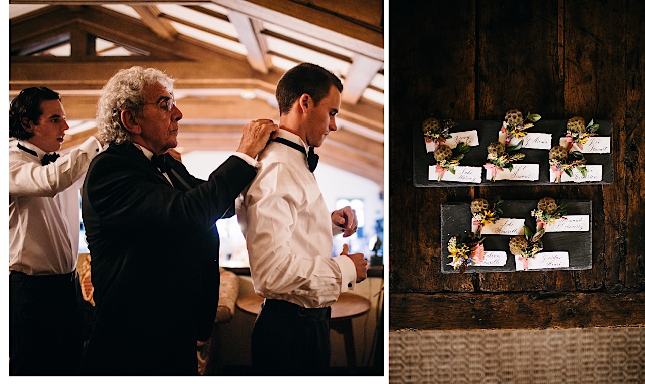 older groomsman helps another groomsman put on his bow tie and boutonnieres sit on slate tablets