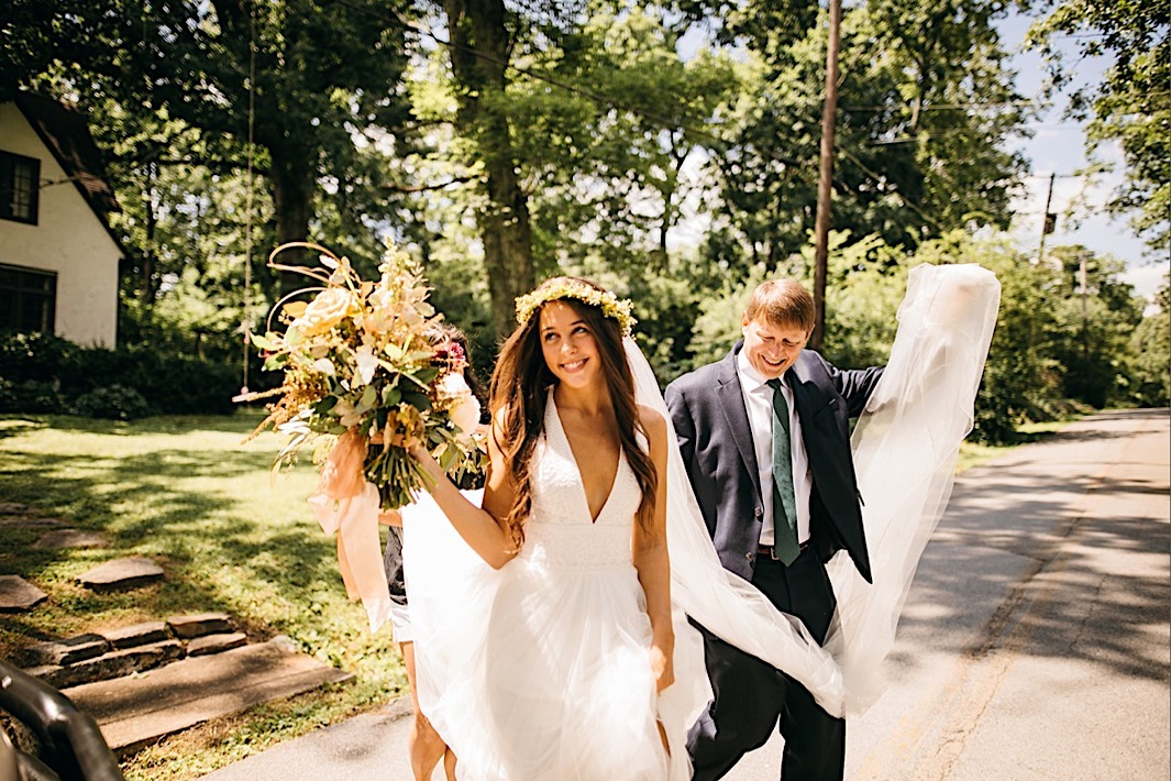 bride holds her bouquet and walks across a street while her father carries her long veil behind her
