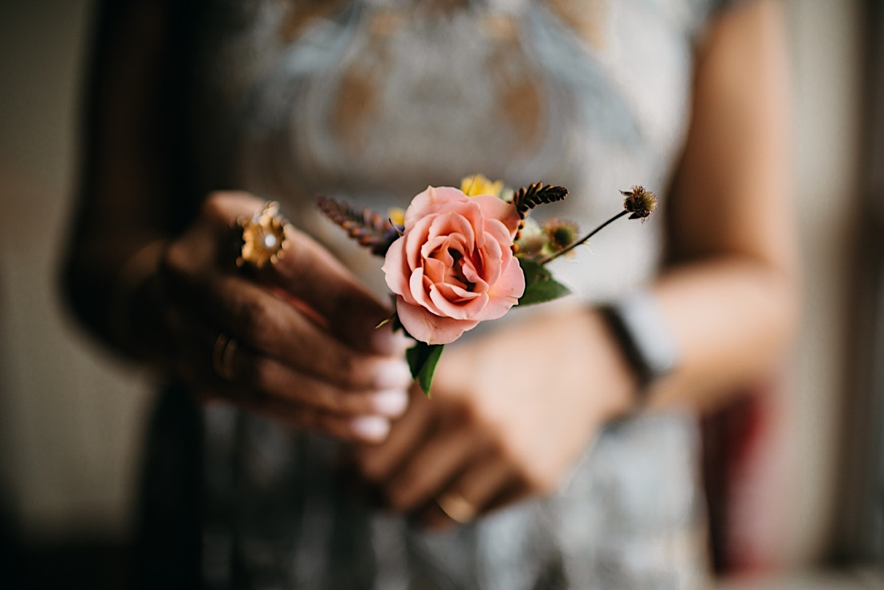 woman holds small pink flower boutonniere by Emily Kaye Designs