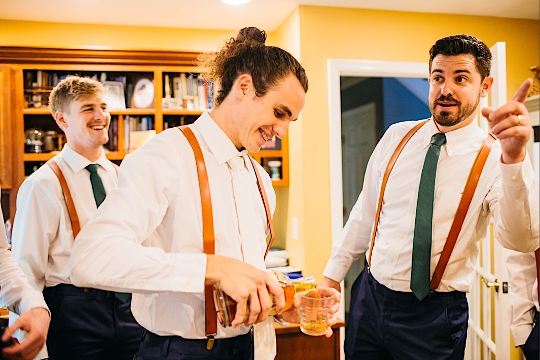 groom wearing white shirt and tie and brown suspenders pours Chattanooga Whiskey into a glass while groomsmen laugh around him