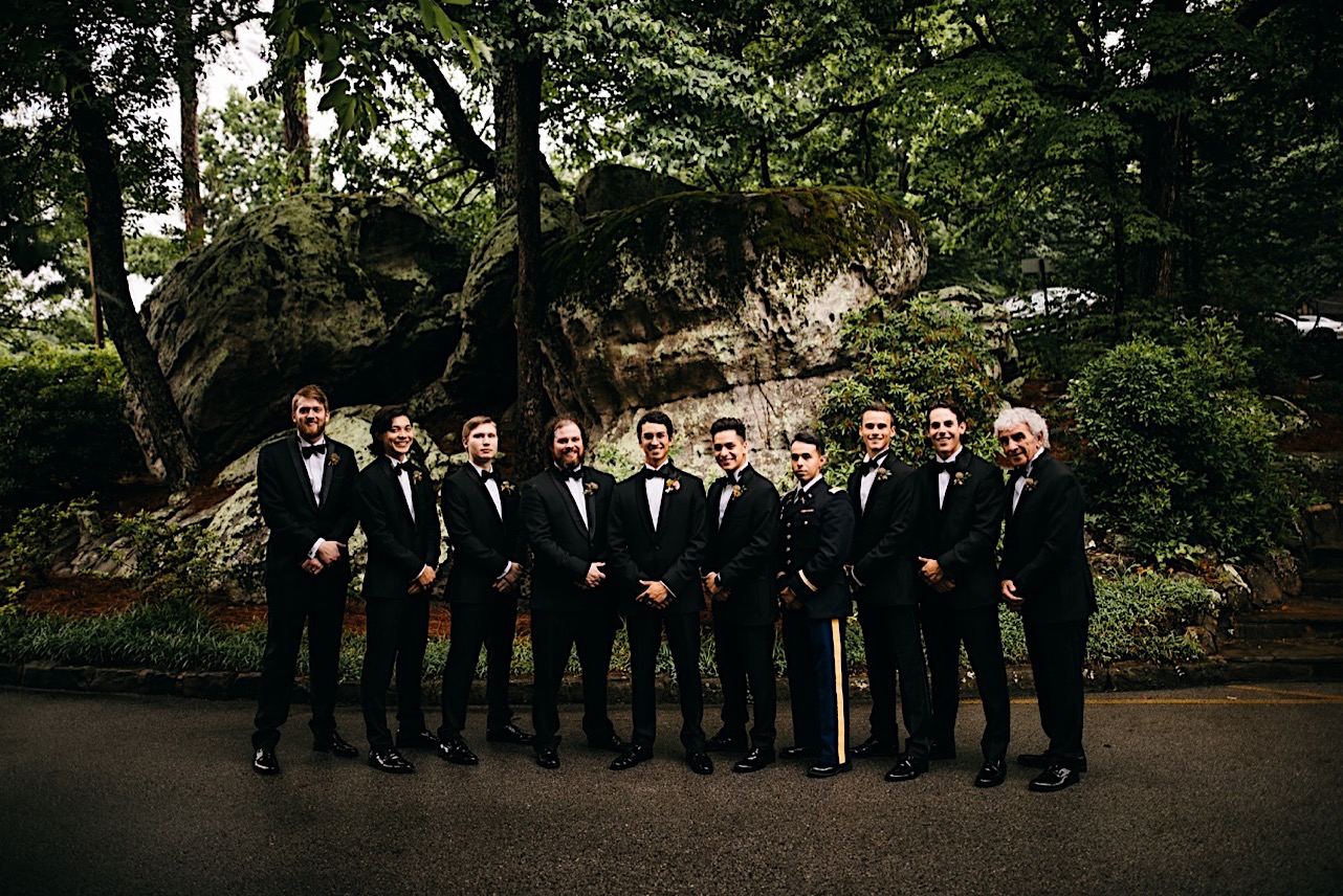 groom stands with groomsmen in front of large rocks on Lookout Mountain